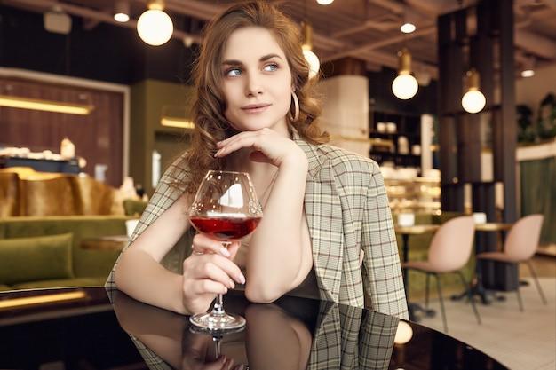 Elegante mujer morena hermosa con copa de vino tinto