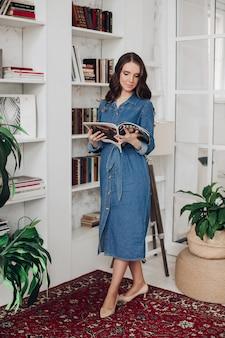 Elegante mujer morena hermosa en vestido de mezclilla y tacones leyendo una revista