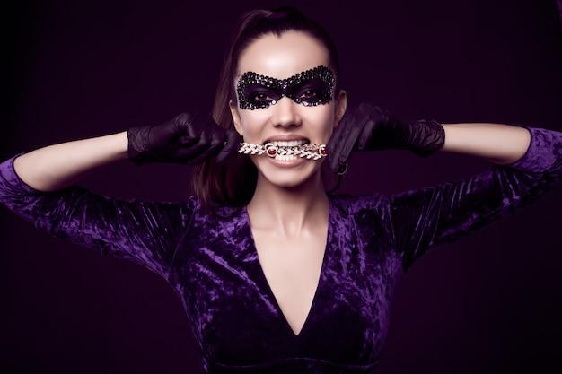 Elegante mujer morena con hermoso vestido morado, máscara de lentejuelas y guantes negros