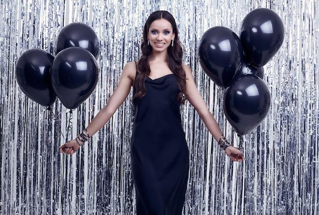 Elegante mujer morena hispana en lujoso vestido negro tiene globos