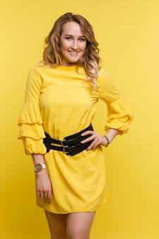 Elegante mujer morena con vestido amarillo y tacones.
