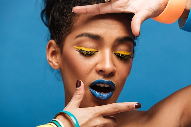 Elegante mujer mulata horizontal con maquillaje colorido y cabello rizado en moño cogidos de la mano cerca de la cara aislada, sobre pared azul