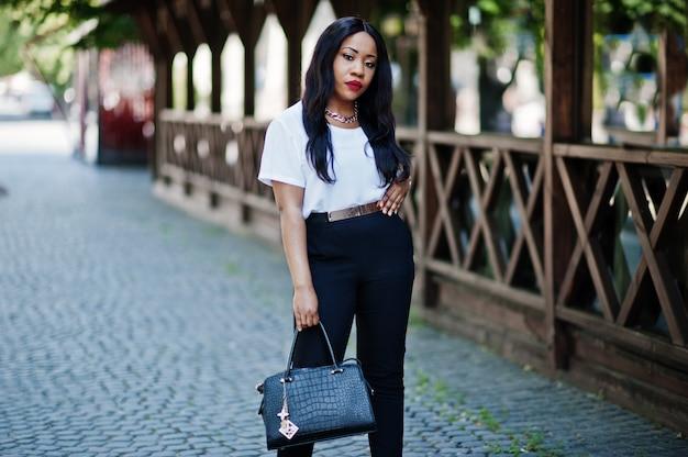 Elegante mujer de negocios afroamericano con bolso en las calles de la ciudad.