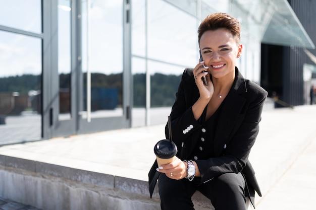 Elegante mujer de negocios en la superficie de un edificio de oficinas de moda