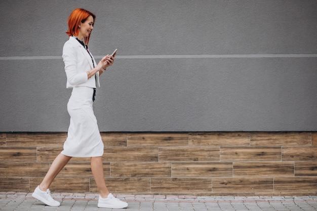 Elegante mujer de negocios en traje blanco hablando por teléfono