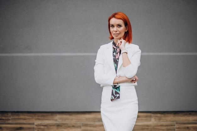 Elegante mujer de negocios en traje blanco sobre fondo gris