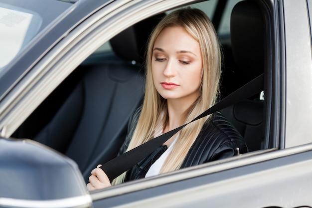 Elegante mujer de negocios vestida con el traje que se abrocha el cinturón de seguridad antes de conducir su automóvil