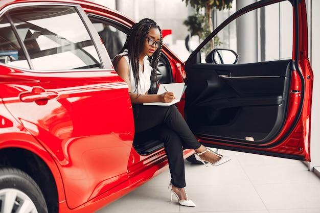 Elegante mujer negra en un salón de autos.
