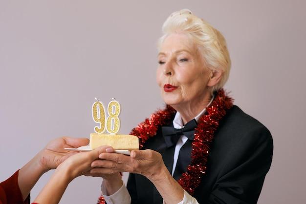 Elegante mujer de noventa y ocho años en traje negro celebrando su cumpleaños con tarta