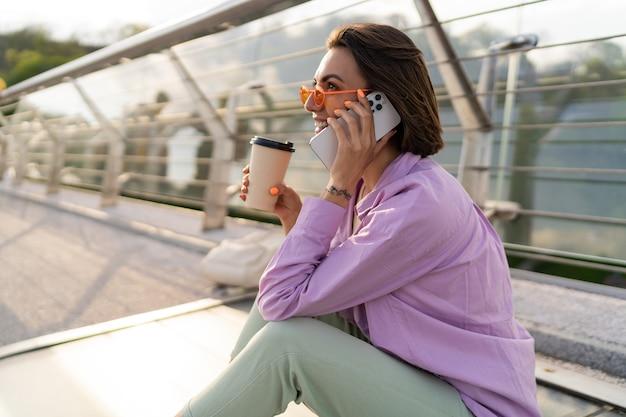 Elegante mujer de pelo corto sentada en un puente moderno, disfrutando de un café y usando un teléfono móvil