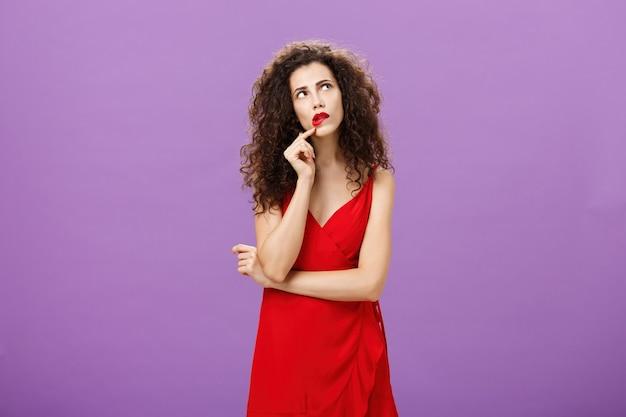 Elegante mujer pensativa en vestido rojo de moda con peinado rizado y maquillaje de fiesta tocando el labio mirando en la esquina superior derecha pensando cómo causar impresión durante la conversación sobre fondo morado.