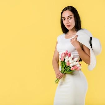 Elegante mujer de pie con flores.