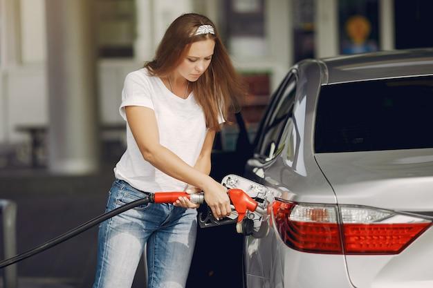 Elegante mujer de pie en una gasolinera