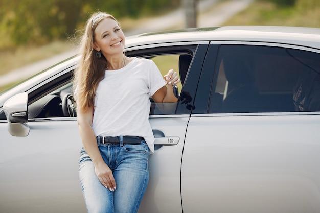 Elegante mujer de pie junto al auto
