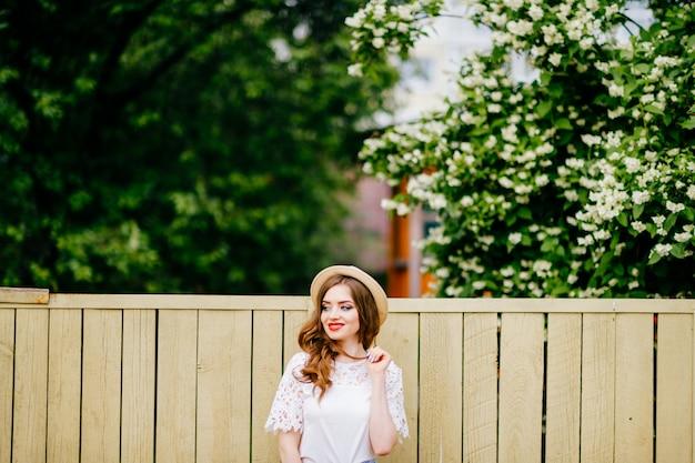 Elegante mujer posando al aire libre con valla y árboles detrás de ella.