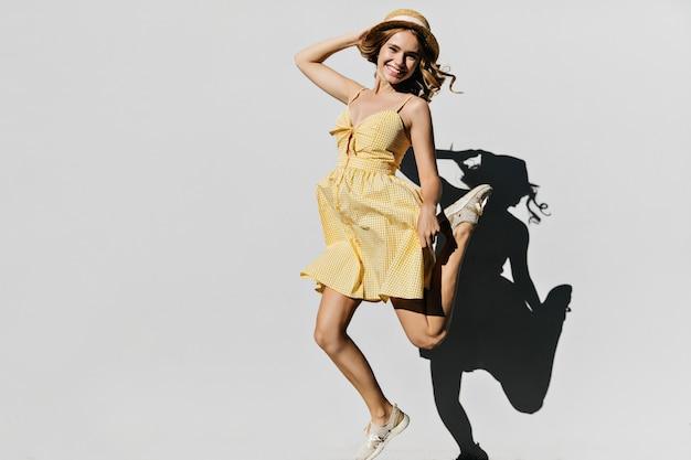 Elegante mujer rizada jugando durante la sesión de fotos de verano y riendo. retrato de niña blanca sin preocupaciones en traje de verano saltando con una sonrisa.