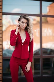 Elegante mujer rubia en traje rojo oscuro con botones dorados