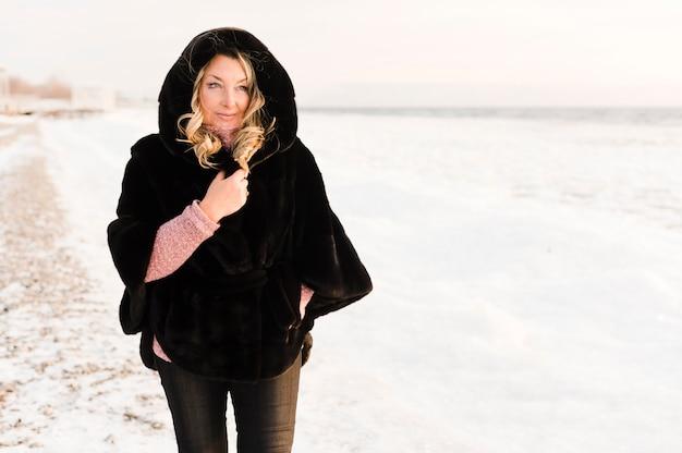 Elegante mujer senior disfrutando de la nieve
