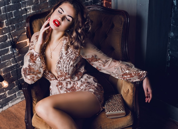 Elegante mujer sensual sentada en un lujoso sillón