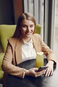 Elegante mujer sentada en la mesa con cóctel y teléfono