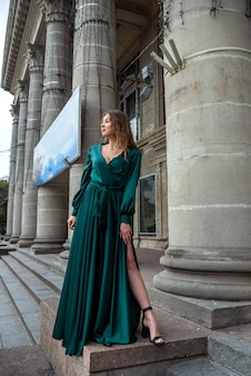 Elegante mujer sexy en vestido largo verde posando junto a la columna del teatro de la ciudad