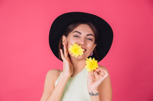 Elegante mujer con sombrero, sonriendo con dos ásteres amarillos, lindo sostener una flor en la boca, humor primaveral, emociones felices espacio aislado