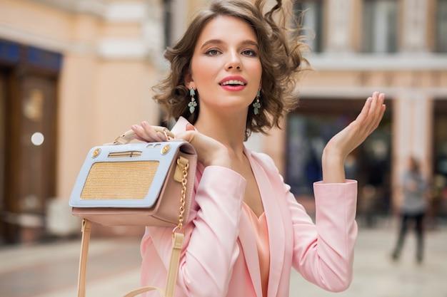 Elegante mujer sonriente atractiva con peinado rizado caminando en la ciudad con elegante bolso en rosa