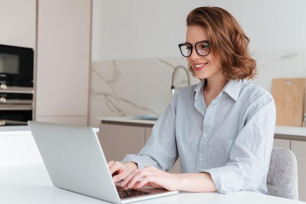 Elegante mujer sonriente en gafas y camisa a rayas usando la computadora portátil mientras se sienta a la mesa en la cocina