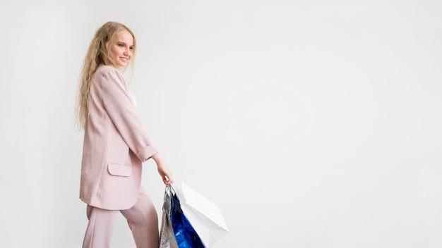 Elegante mujer sosteniendo bolsas con espacio de copia