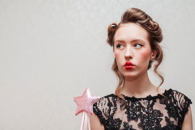 Elegante mujer sosteniendo una estrella en el palo
