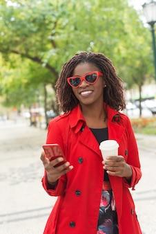 Elegante mujer con teléfono inteligente riendo en el parque