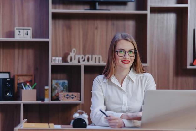 Elegante mujer trabaja con una computadora portátil en una oficina moderna