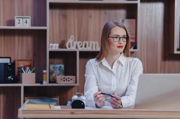 Elegante mujer trabaja en un escritorio portátil en una oficina moderna