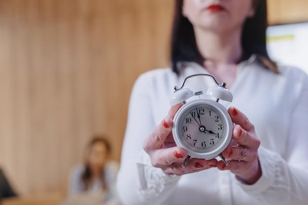 Elegante mujer trabajadora de oficina con gafas con un despertador clásico en las manos sobre fondo de colegas de trabajo