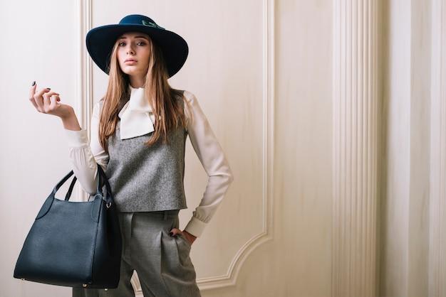 Elegante mujer en traje y sombrero con bolso en habitación.