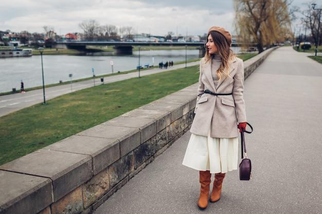 Elegante mujer turista caminando por el muelle por el río wisla en cracovia, polonia, disfrutando del paisaje.