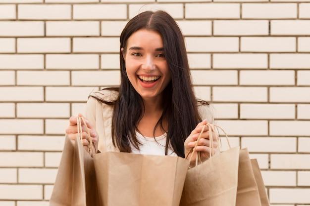 Elegante mujer vestida sosteniendo una bolsa de compras abierta