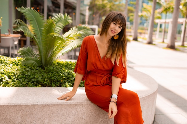 Elegante mujer en vestido naranja posando en el paseo marítimo con palmeras y rascacielos en la gran ciudad moderna
