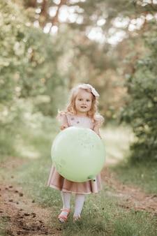Elegante niña de 4-5 años sosteniendo un globo grande con un vestido rosa de moda en la pradera. juguetón. niña con un globo en el parque. fiesta de cumpleaños.