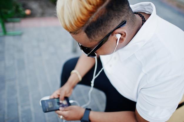 Elegante niño musulmán árabe con originalmente cabello y gafas de sol en las calles, sentado en un banco y escuchando música desde los auriculares del teléfono.