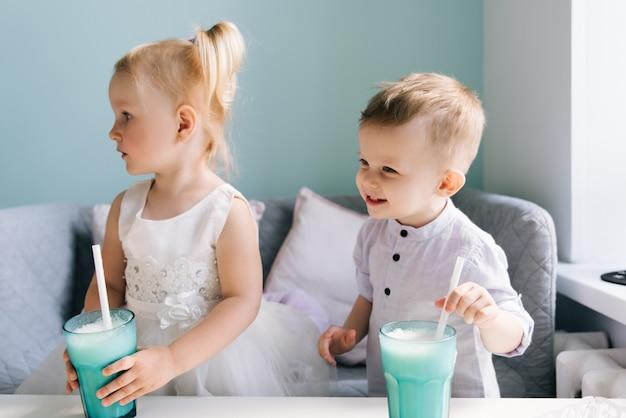 Elegante niño y niña en un café infantil bebiendo un batido