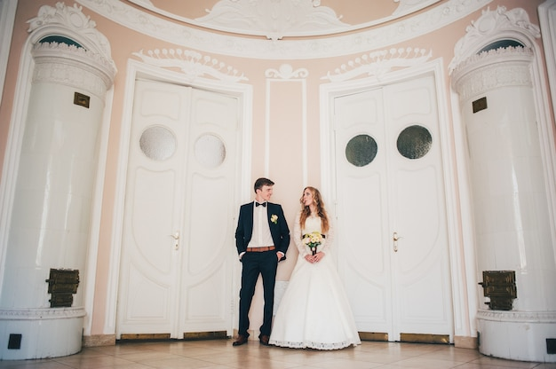 Una elegante novia elegante con ramo de flores de la boda y el novio de pie en el fondo de la pared.