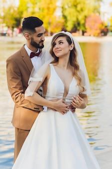 Elegante novia feliz y el novio posando en la gran palabra de amor en la luz del atardecer en la recepción de la boda al aire libre. hermosa pareja de recién casados divirtiéndose en el parque de noche.