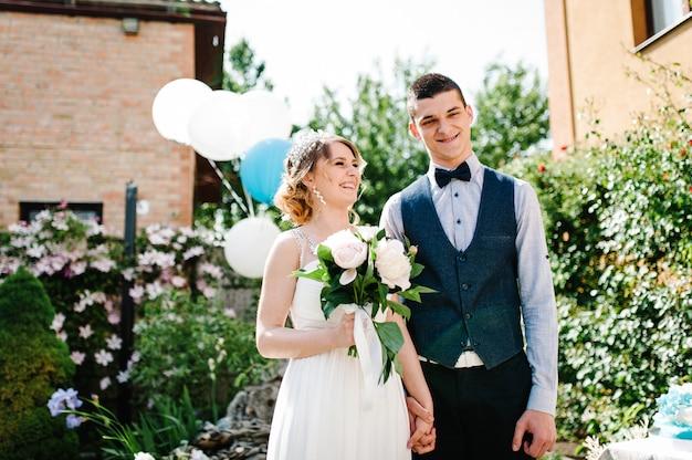 Elegante novia feliz con un ramo de peonías y el novio de la mano.