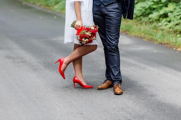 Elegante novia en vestido blanco con encaje con ramo de flores de novia y novio en traje azul