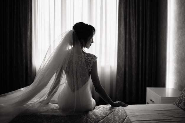 Elegante novia en un vestido de novia se sienta en una cama en un hotel frente a la ventana. boda mañana de la novia.