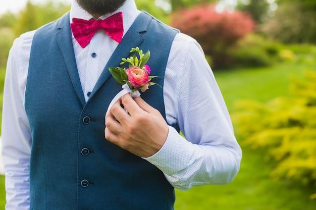 Elegante novio tocando su flor en el ojal