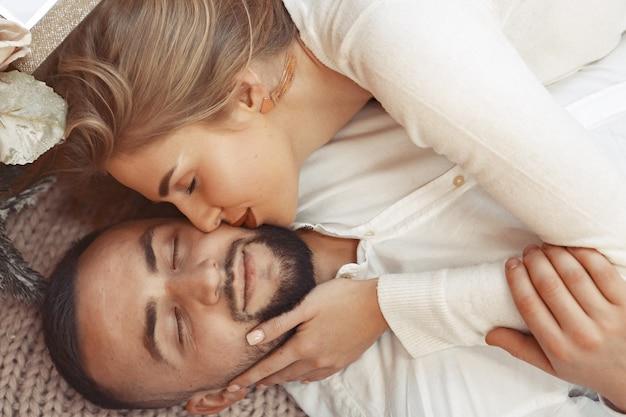 Elegante pareja acostada en una cama en casa