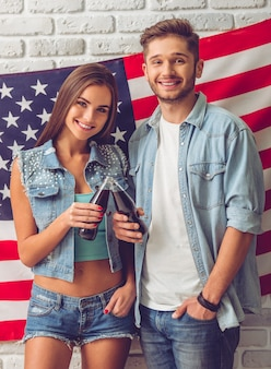 Elegante pareja adolescente sosteniendo una botella de agua de soda
