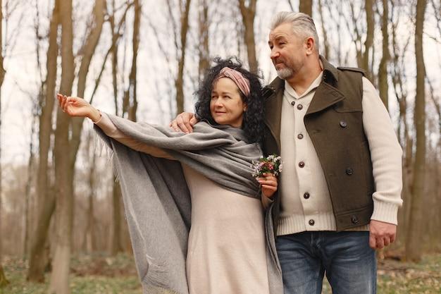 Elegante pareja adulta en un bosque de primavera